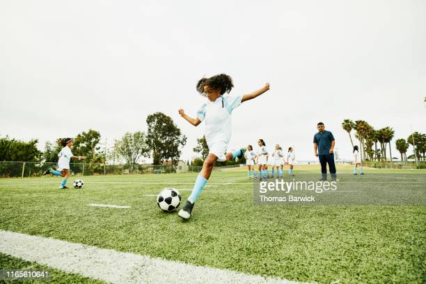 coach watching young female soccer player practicing shot before game - calcio sport foto e immagini stock