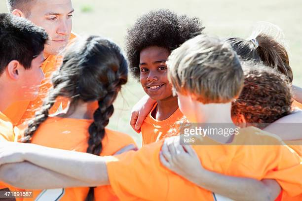 Entrenador con equipo de deportes para niños