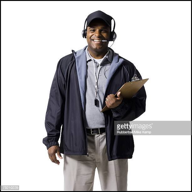 Coach with clipboard and headset smiling
