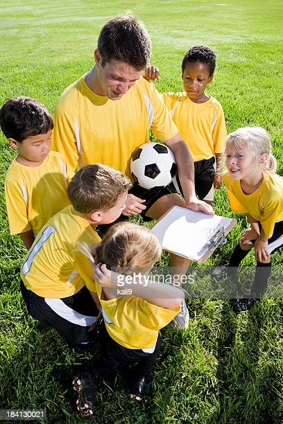 Coach with diverse team of young children playing soccer