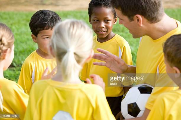 コーチ、多様な若いチームのサッカー選手