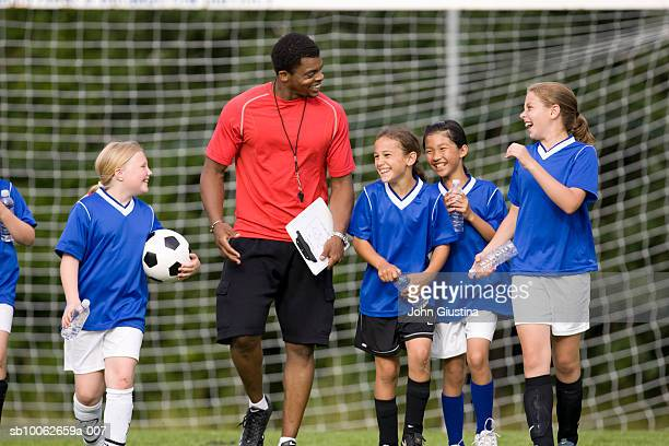 coach with girls (8-13) football team, smiling - coach stock pictures, royalty-free photos & images