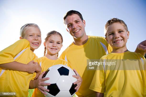 Coach with soccer ball and team of young children