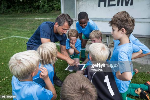 coach with tablet and young football players on football ground - tenue de football photos et images de collection