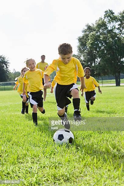 Entrenador con equipo de jóvenes jugando atrapar pelota de fútbol