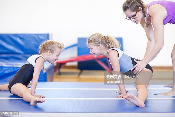 Coach with two girls doing gymnastics exercise on floor