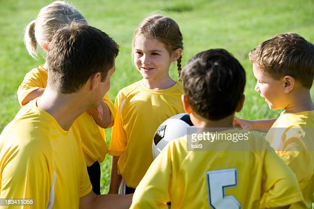 Coach with young team of soccer players