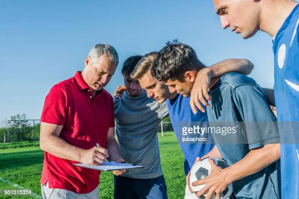 coach with young team of soccer players - pep talk stock pictures, royalty-free photos & images