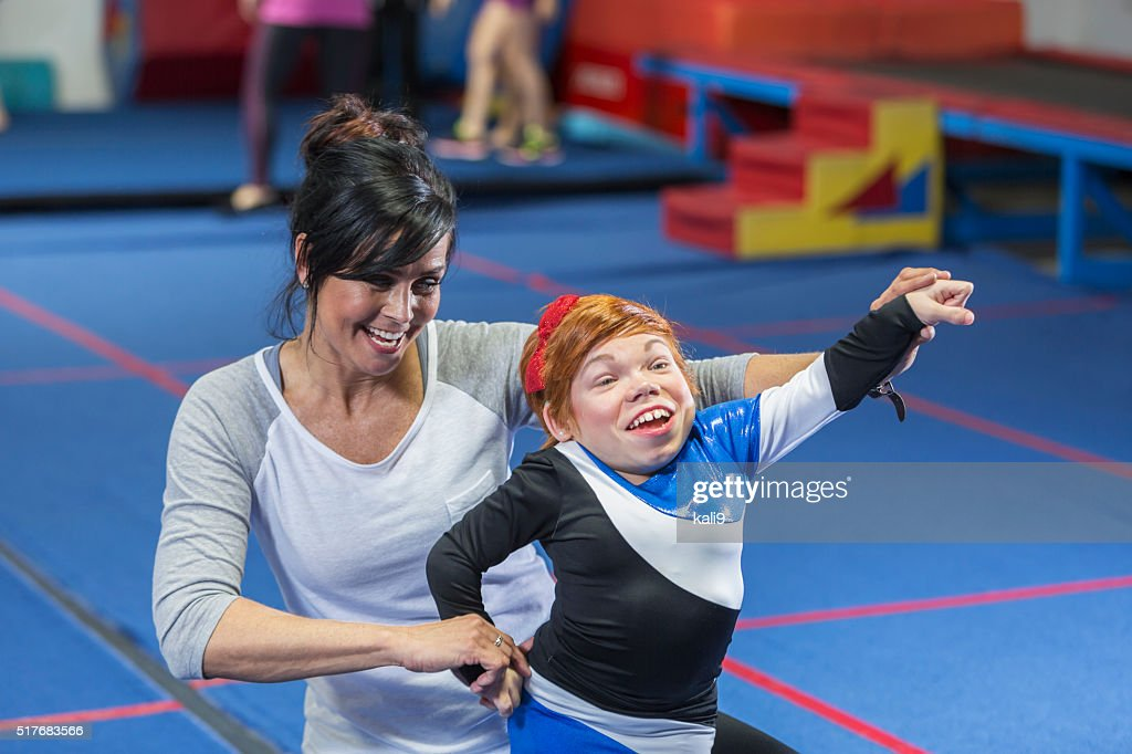 Coach working with cheerleader on special needs team : Stock Photo