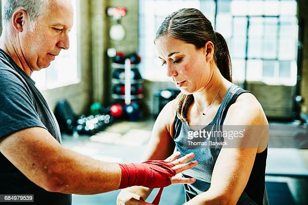 Coach wrapping mans hands before boxing workout