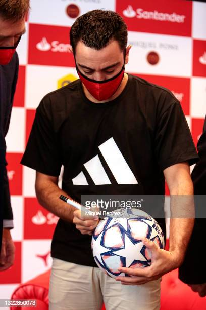 Coach Xavi Hernandez sings a Uefa Champions League's soccer ball during the 'Campus Xavi Hernández by Santander' at Work Cafe on June 10, 2021 in...