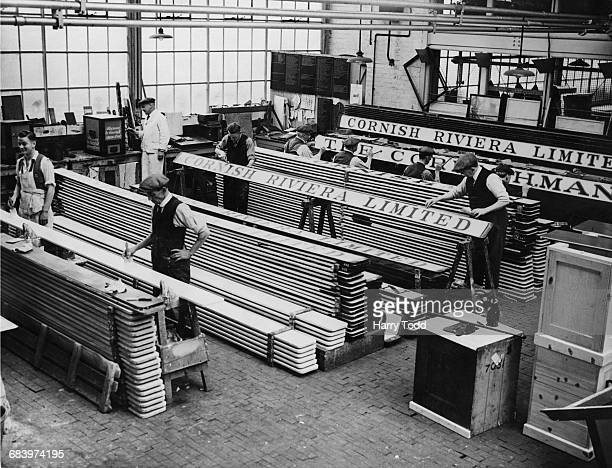 Coachbuilders for Great Western Railway at work on painting the roof label boards on the passenger coaches for the two new Cornish Riviera Express...