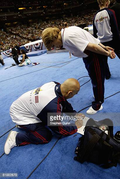 Coaches Al Fong and Armine Barutyan-Fong write a petition for additional points on behalf of Courtney McCool after McCool's floor exercise during the...
