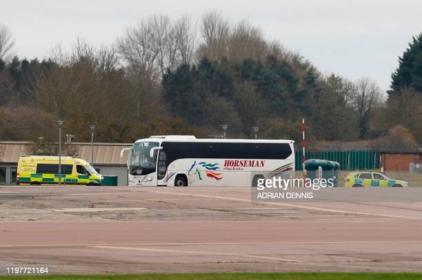 Coaches and ambulances wait on the tarmac ahead of the arrival of a chartered passenger jet carrying evacuated citizens from China at the Royal Air...