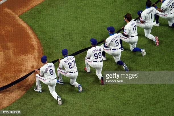 Coaches and players on the Texas Rangers kneel during the national anthem before the game between the Colorado Rockies and the Texas Rangers at Globe...