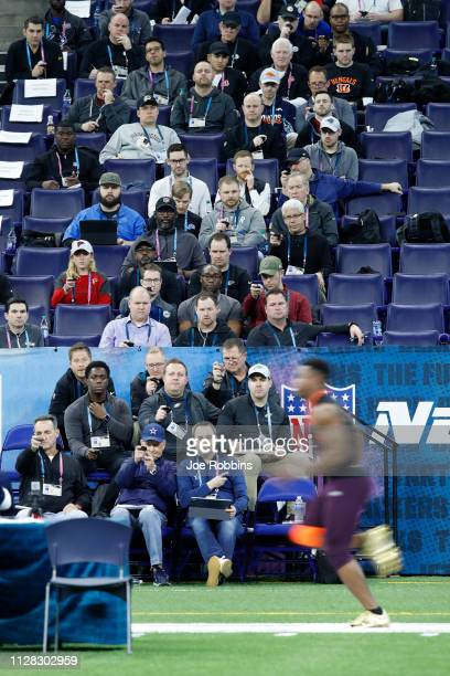 Coaches and scouts from NFL teams time Damien Harris of Alabama as he runs the 40yard dash during day two of the NFL Combine at Lucas Oil Stadium on...