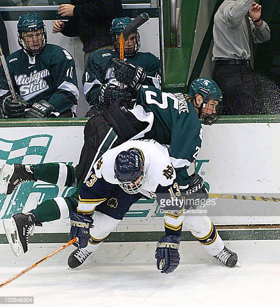 Coaches and trainers guard themselves from a nasty check by Irish senior Tom Galvin on Michigan State junior left wing Brock Radunski