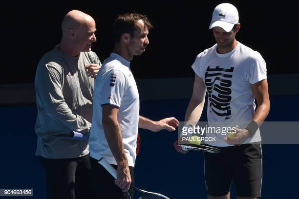 Coaches Andre Agassi and Radek Stepanek talk to Serbia's Novak Djokovic during a practice session ahead of the Australian Open tennis tournament in...