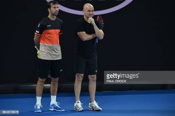 Coaches Andre Agassi and Radek Stepanek watch Serbia's Novak Djokovic during a practice session ahead of the Australian Open tennis tournament in...