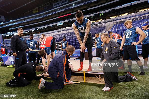 Coaches are seen measuring wide receivers during the 2013 NFL Combine at Lucas Oil Stadium on February 24 2013 in Indianapolis Indiana