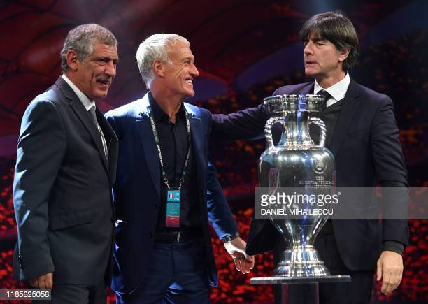 Coaches from Group F teams pose behind the trophy during the UEFA Euro 2020 football competition final draw in Bucharest on November 30, 2019 : head...