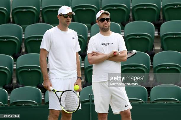 Coaches Ivan Ljubicic and Severin Lüthi watch Roger Federer of Switzerland practices on court during training for the Wimbledon Lawn Tennis...