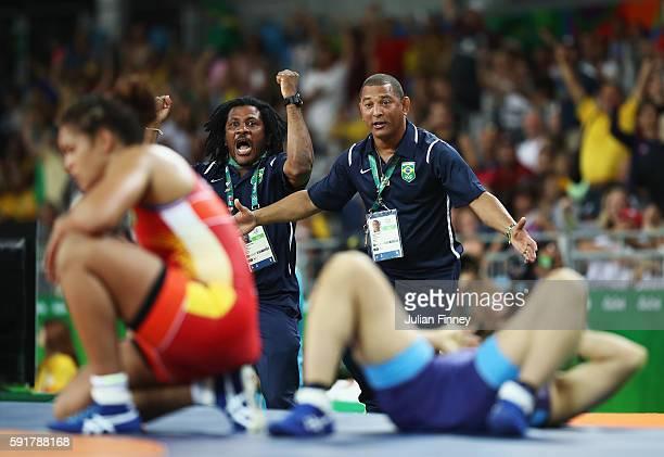 Coaches Pedro Miguel Perez and Angel Aldama celebrate after Aline da Silva Ferreira of Brazil defeats Rio Watari of Japan during the Women's...