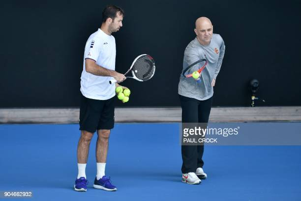 Coaches Radek Stepanek and Andre Agassi talk during a practice session with Serbia's Novak Djokovic ahead of the Australian Open tennis tournament in...