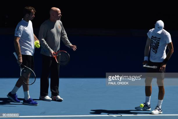 Coaches Radek Stepanek and Andre Agassi talk to Serbia's Novak Djokovic during a practice session ahead of the Australian Open tennis tournament in...