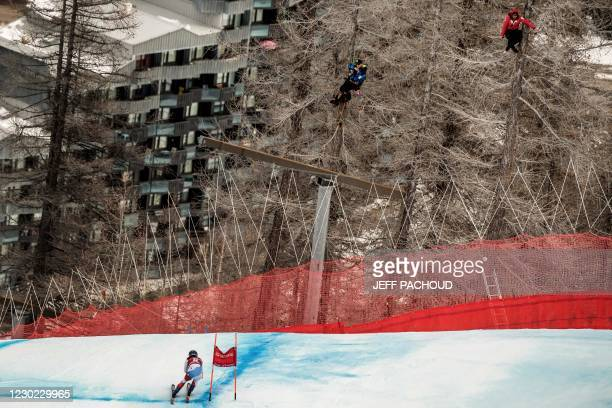 Coaches sit in trees to watch the race during the womens Super G event of the FIS Alpine Ski World Cup in Val dIsere, French Alps, on December 20,...