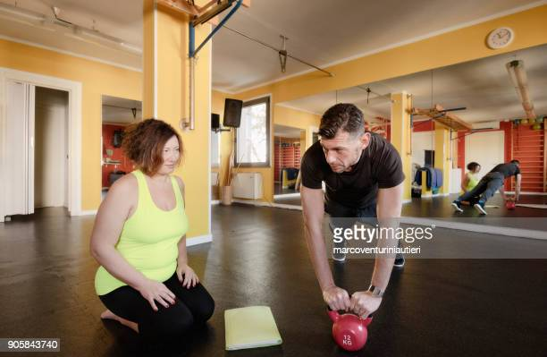 coaching a curvy woman in the fitness centre