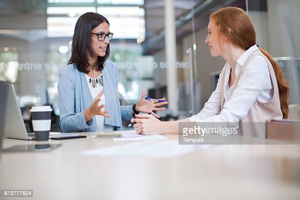 coaching and advise, two business woman working together. - enseigner photos et images de collection