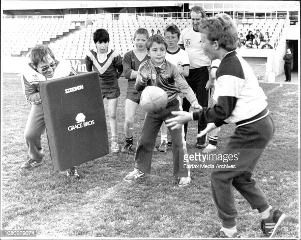 Coaching session for young football children at Parramatta StadiumRoy Masters with tackle pad as John Plattner passes to Jim Langley both 9 from...