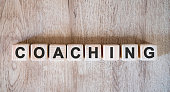 Coaching text word on wooden cubes on wooden background