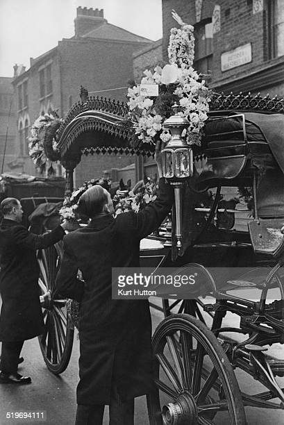 A coachman attaches a wreath to the hearse before moving off during the funeral for Battersea street trader Jim Lloyd Battersea London 23rd April...