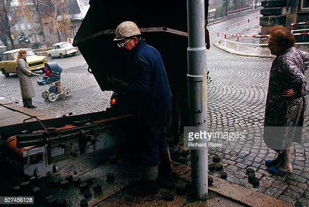 A coal delivery man deposits chunks of brown coal into the cellar via a conveyor belt for an elderly lady who stands outside in the bitter cold...
