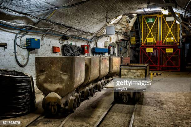 coal mine underground corridor with freight railroad cars and elevator mine shaft - mine elevator stock pictures, royalty-free photos & images