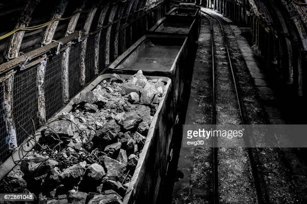 coal mine underground corridor with railway carriages and hard coal - coal mining foto e immagini stock