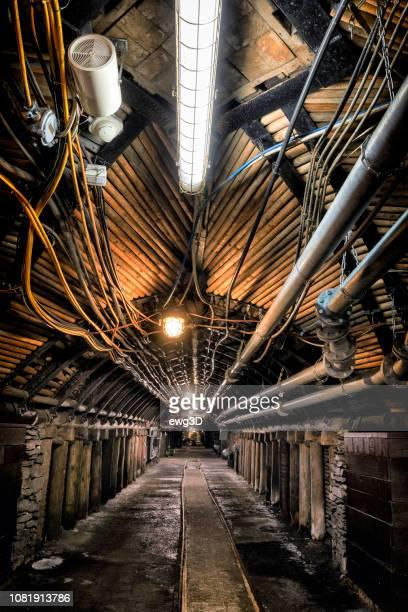coal mine unterirdischen korridor mit stahl-support-system und elektrische geräte - unterirdisch stock-fotos und bilder