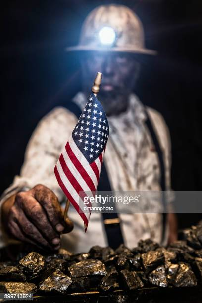 coal miner covered in coal dust holding a small us flag looking at the camera - coal miner stock photos and pictures