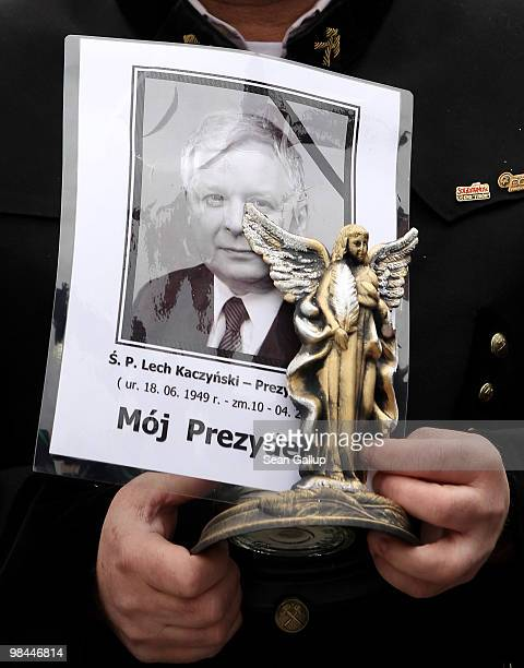 A coal miner from the southern Polish city of Katowice holds a portrait of late Polish President Lech Kaczynski as he stands in line to pay his last...
