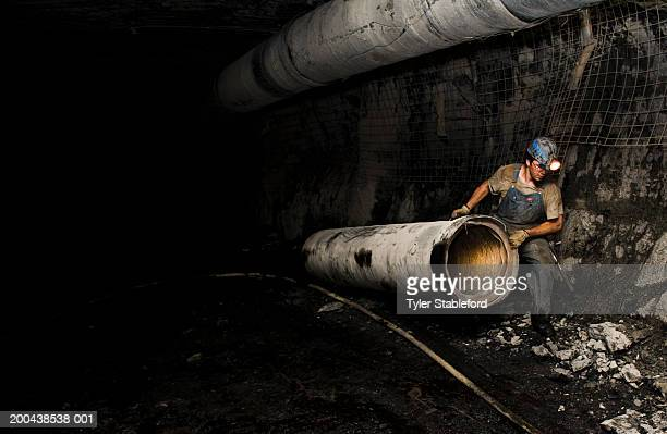 coal miner hauling ventilation tube throuh mine, side view - coal mine stock pictures, royalty-free photos & images