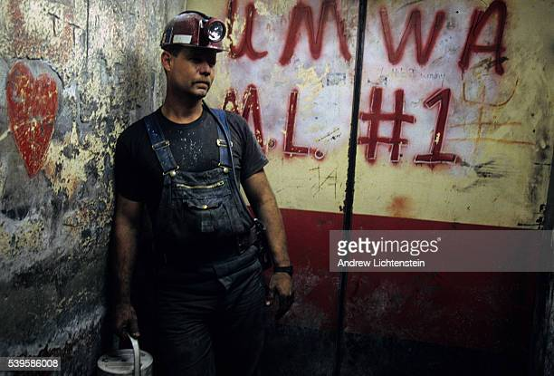 A coal miner in a mine shaft with union grafitti spray painted on an elevator door