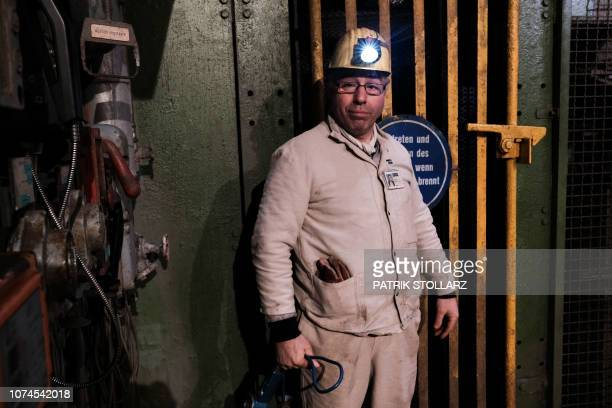 Coal miner Mehmet Kalyoncu poses in front of the elevator after the last piece of black coal was coaled at the Prosper Haniel colliery on December 21...