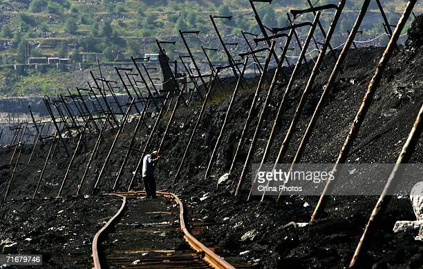 A coal miner monitors tracks in an open pit coal mine on August 19 2006 in Chifeng of Inner Mongolia Autonomous Region China Pingzhuang Coal Groups...