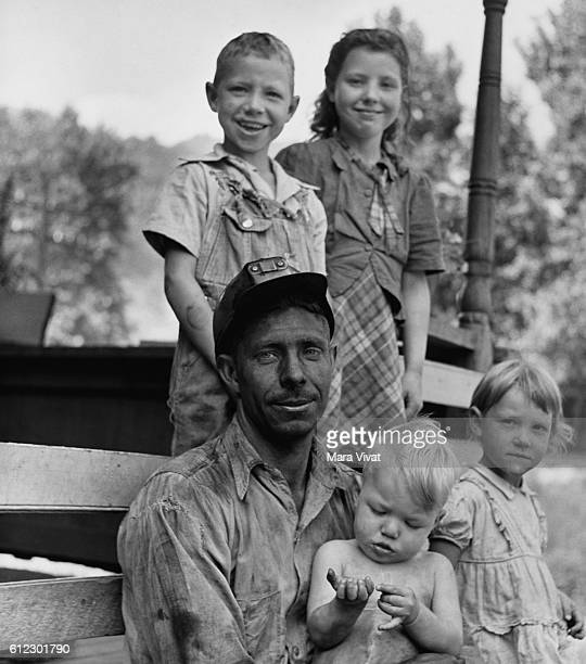 A coal miner rests on his porch with his four children after work in West Virginia USA