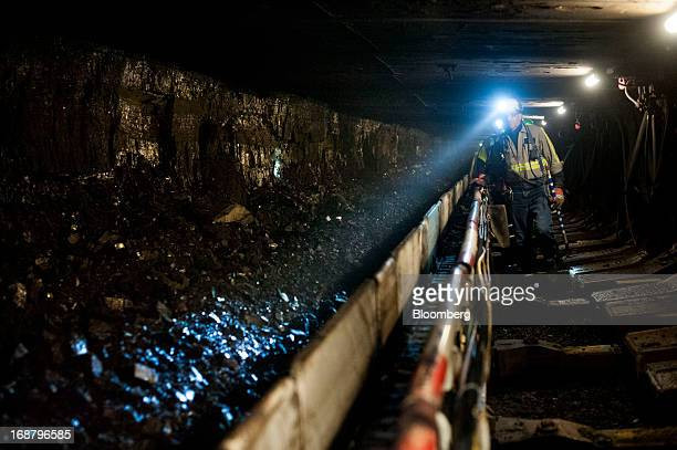 A coal miner shines his head lamp on coal transported on a conveyor belt after being sheared off the wall during longwall mining operations at the...