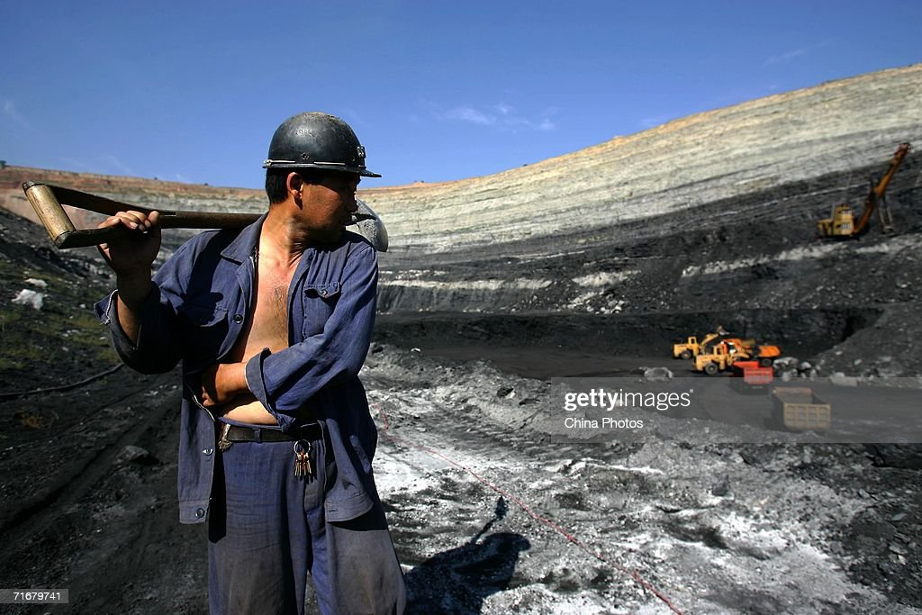 A coal miner walks on coal seams in an open pit coal mine on August 19, 2006 in Chifeng of Inner Mongolia Autonomous Region, China. Pingzhuang Coal Groups Company, including six open pit coal mines, produces 10 million tons per year. Reportedly, in the first four months of this year, China's coal consumption rose by 13.8 percent over the same period of last year, and coal price is expected to go up steadily with the factors of environment, safety and resources included in the cost of coal production.