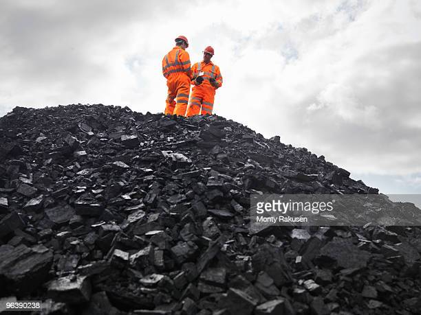 coal miners on pile of coal - coal mine stock pictures, royalty-free photos & images
