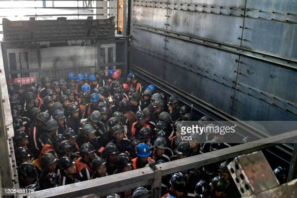 Coal miners stand in a shaft elevator as they wait to descend underground at a coal mine operated by Beijing Haohua Energy Resource Co Ltd on...